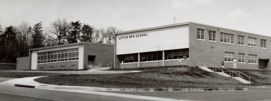 Black and white photograph of the front of Little Run Elementary School. There are a few small trees, but most of the grounds are bare grass. Two students and an adult can be seen near the building.
